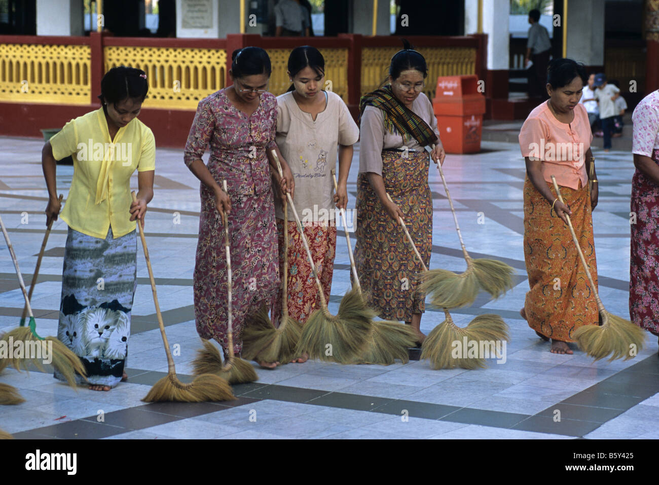 Burmese women ritual cleaning/sweeping at Shwedagon Paya, Burma's most sacred Buddhist site, Rangoon or Yangon, Stock Photo