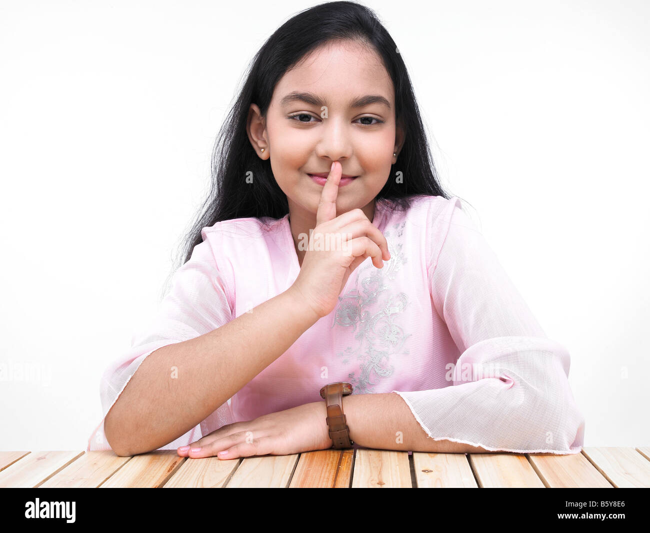 Portrait Of A Cute Asian Teenage Girl Of Indian Origin With Finger On Her Lips