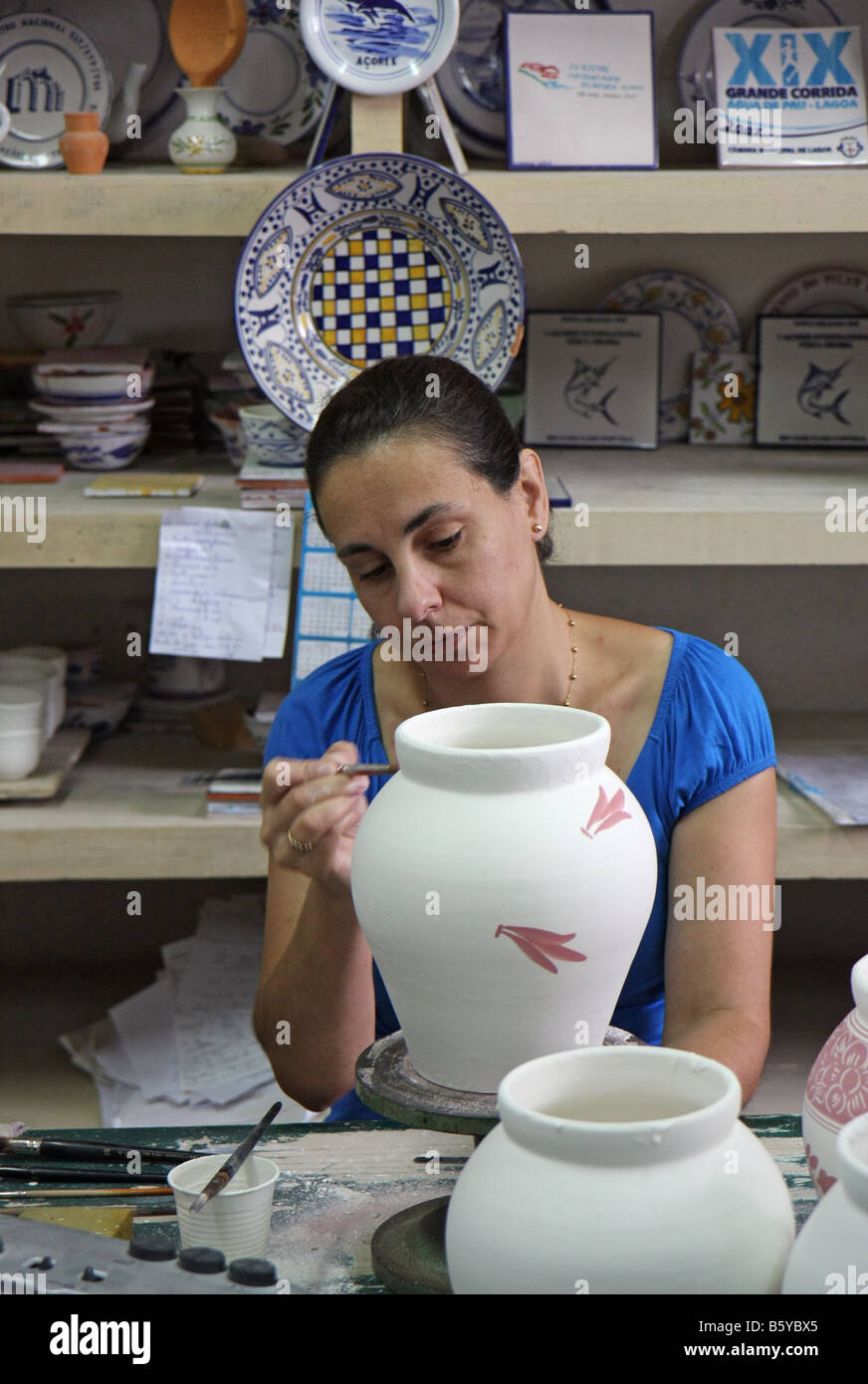 Woman painting at Ceramica vieira pottery in Lagoa, Azores, Portugal. The redish colour becomes blue in the burning - Stock Image
