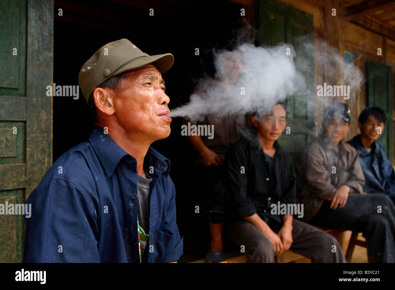 Vietnamese men smoking pipe in front of old house Bac Ha Northern Vietnam - Stock Image