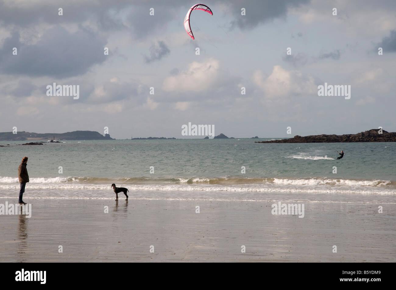 un promeneur regarde un kitesurfer sur la plage Stock Photo