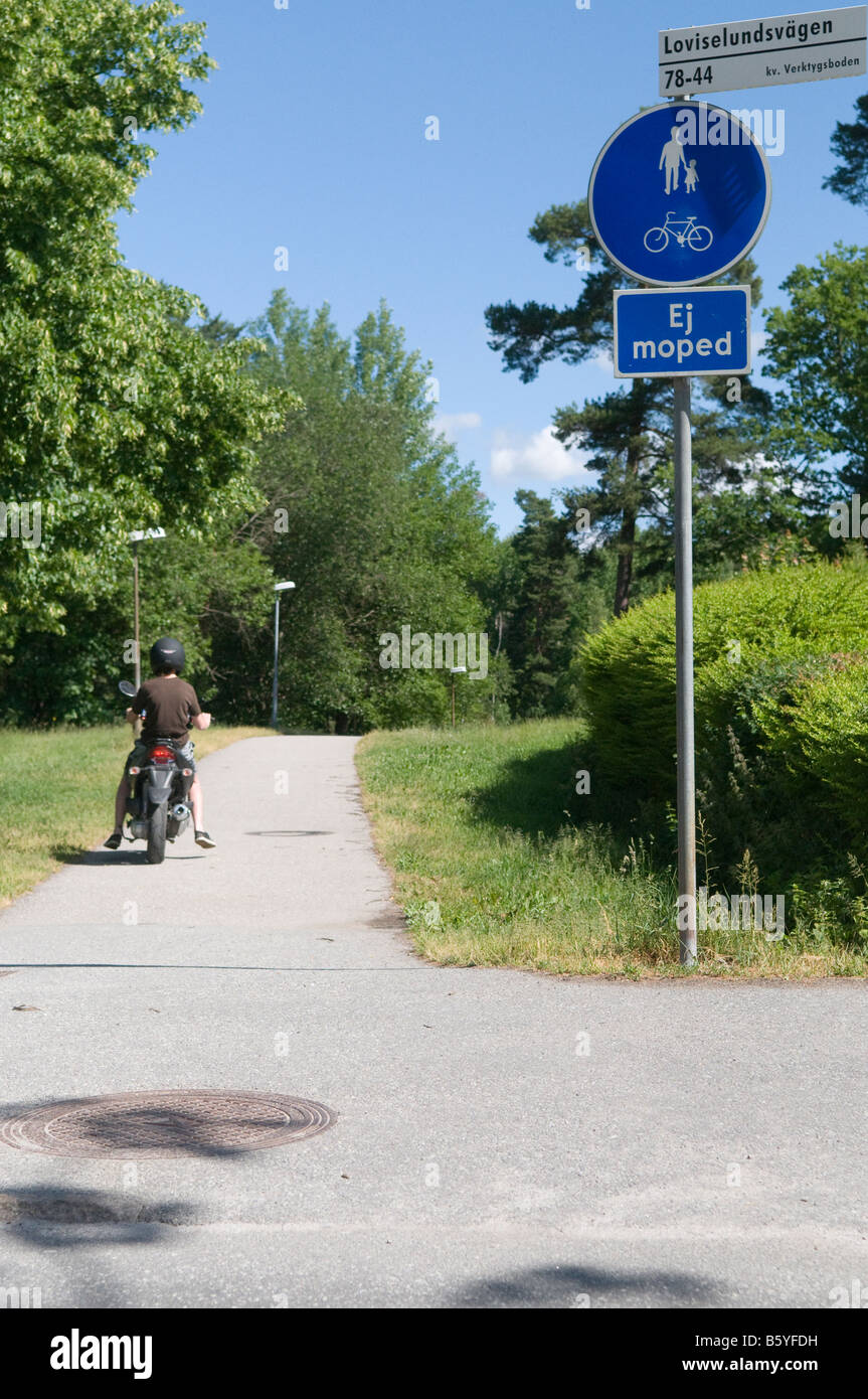 Boy driving a moped. Moped driving prohibited. - Stock Image