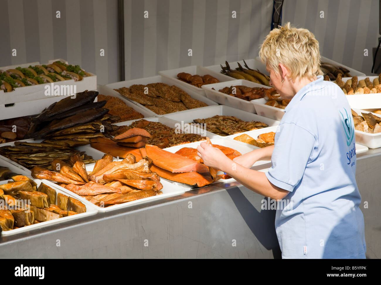 Woman preparing fresh fish for sale on quayside Wismar Germany - Stock Image