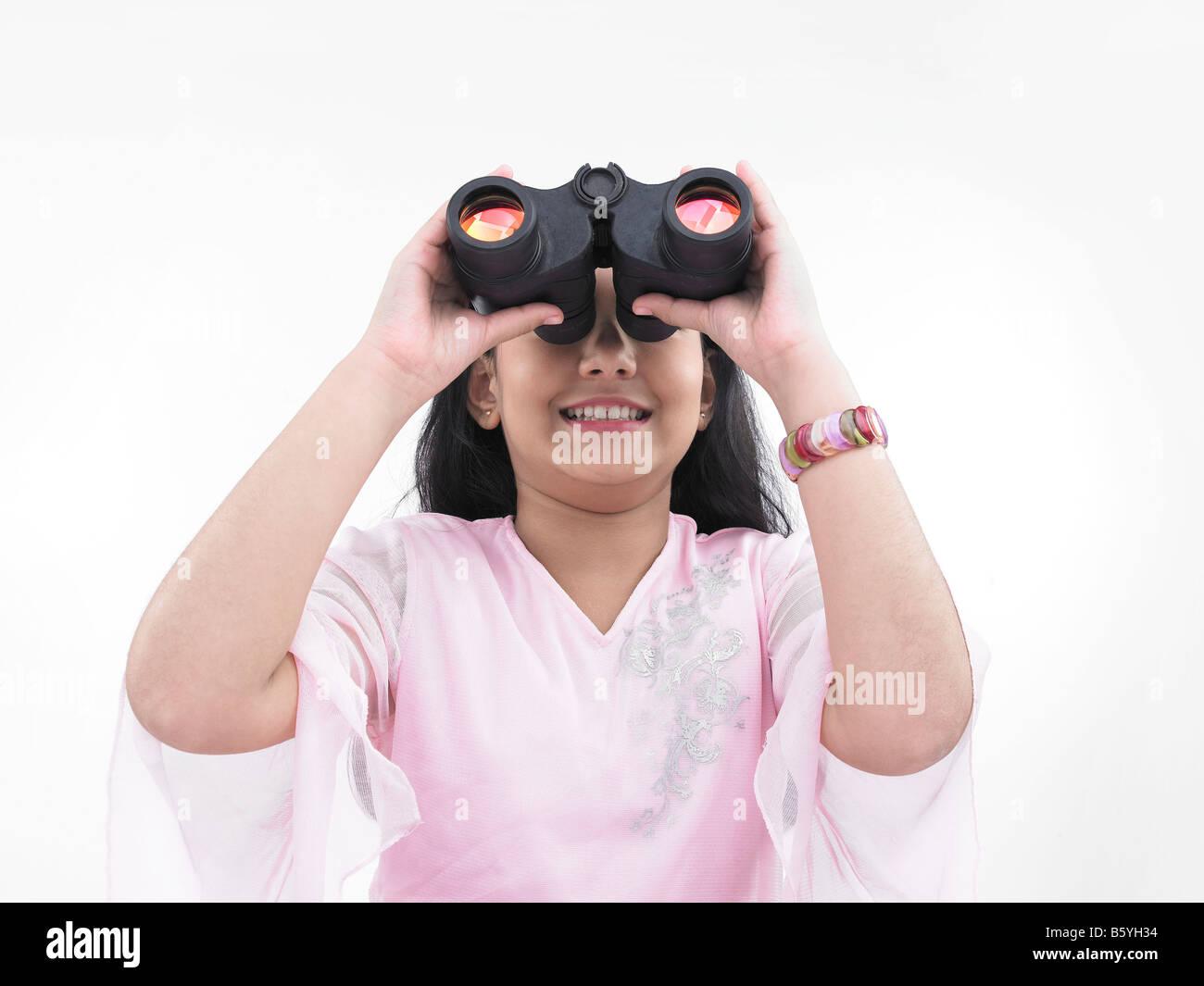 a cute asian teenage girl looking through the binocular - Stock Image