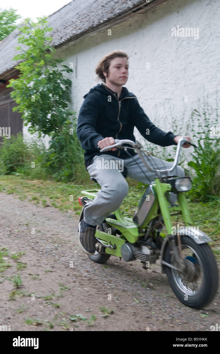 Boy, not wearing a helmet, driving a moped. - Stock Image