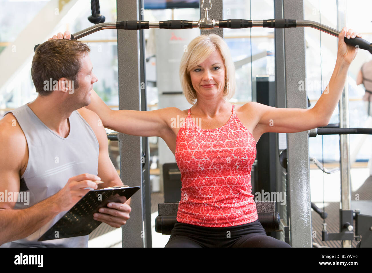 Personal Trainer Watching Woman Weight Train - Stock Image