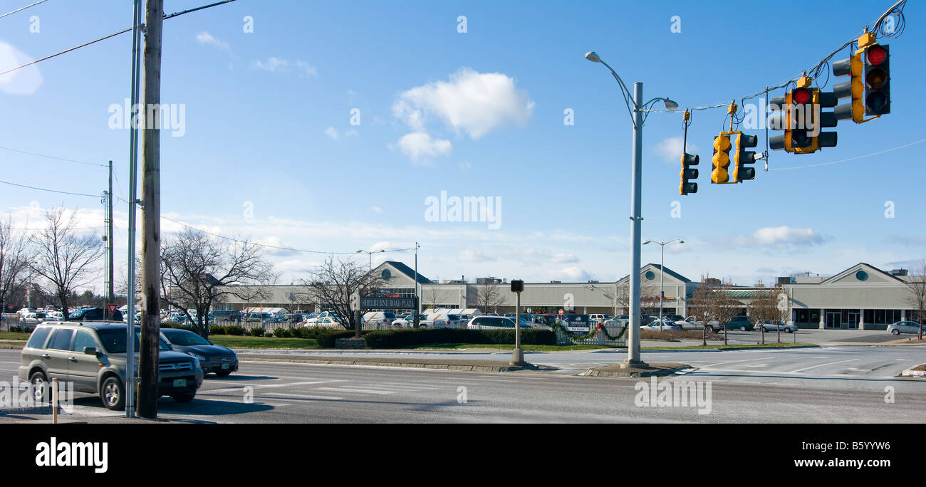 Typical American shopping center or strip mall wide view with traffic lights pavement cars and blue sky Editorial - Stock Image