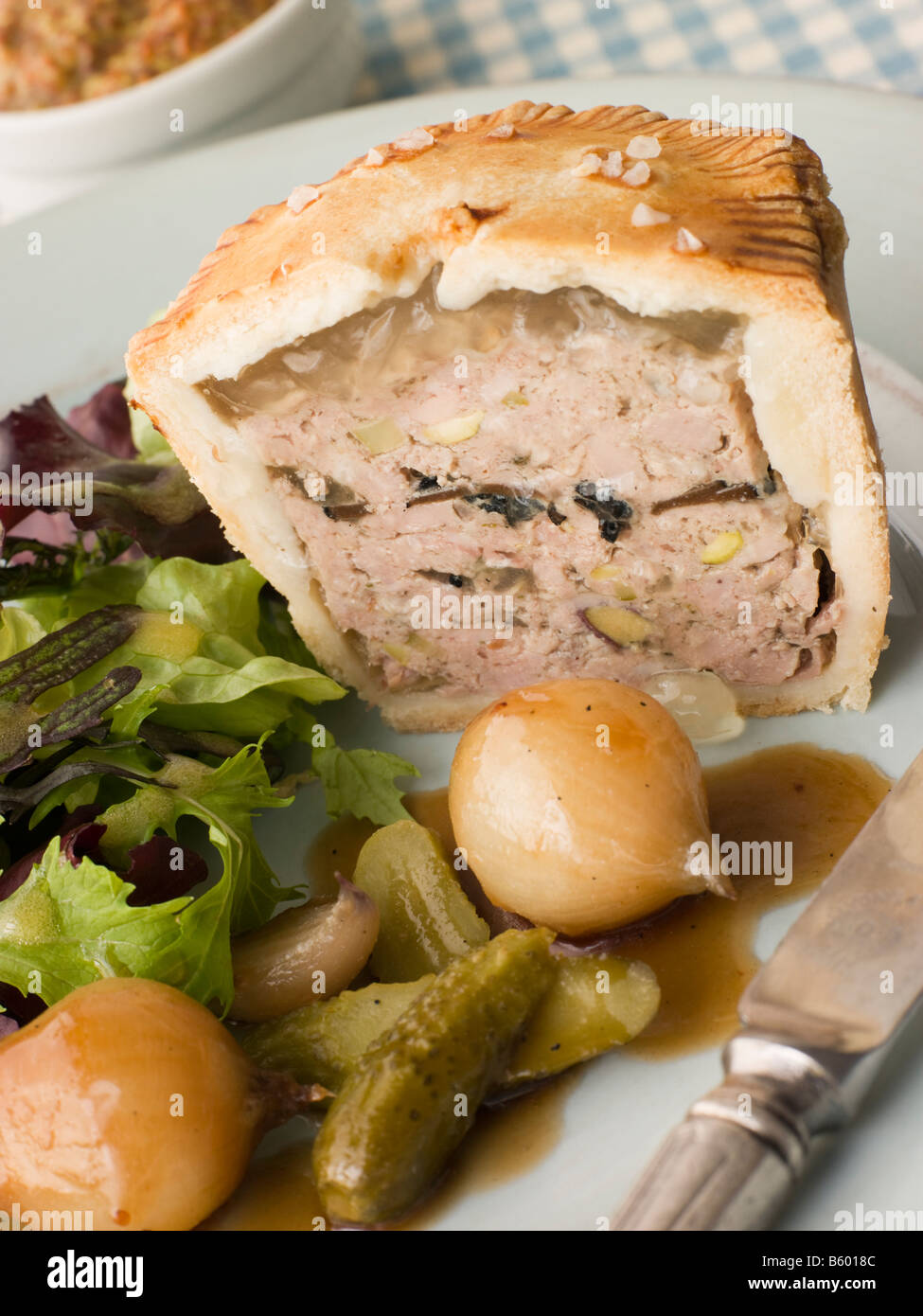 Pork Black Truffle and Pistachio Pie with Glazed Button Onions and Cornichons Stock Photo