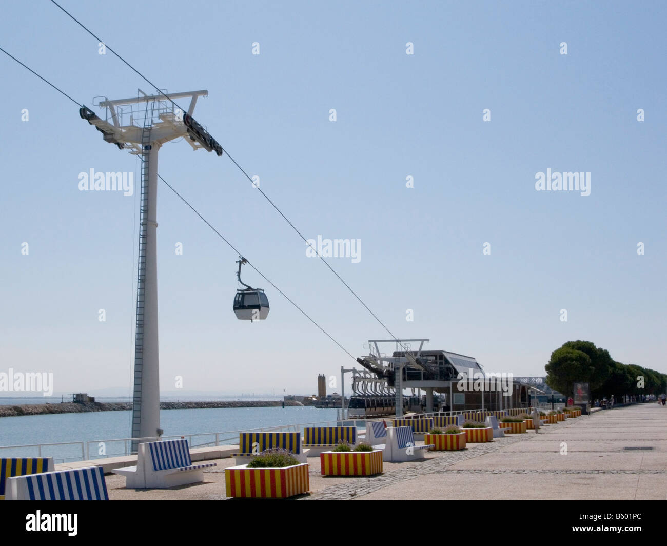 Cable cars and striped benches on the Passeio de Neptuno on the banks of the Tagus, Oriente, Lisbon, Portugal - Stock Image