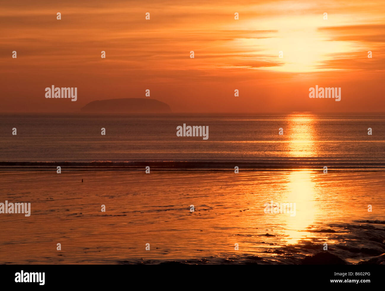 Vivid orange sunset taken from the mudflats at Sandpoint near Weston Super Mare with Steepholm Island visible on - Stock Image