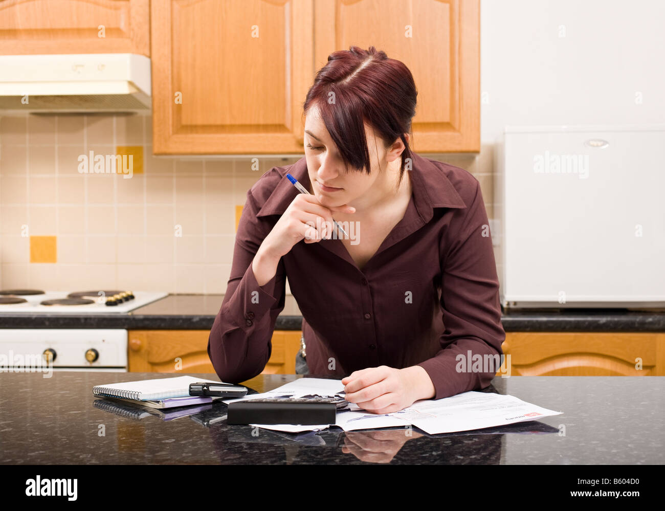 Young woman concentrating on household finances and budget with bills and calculator - Stock Image