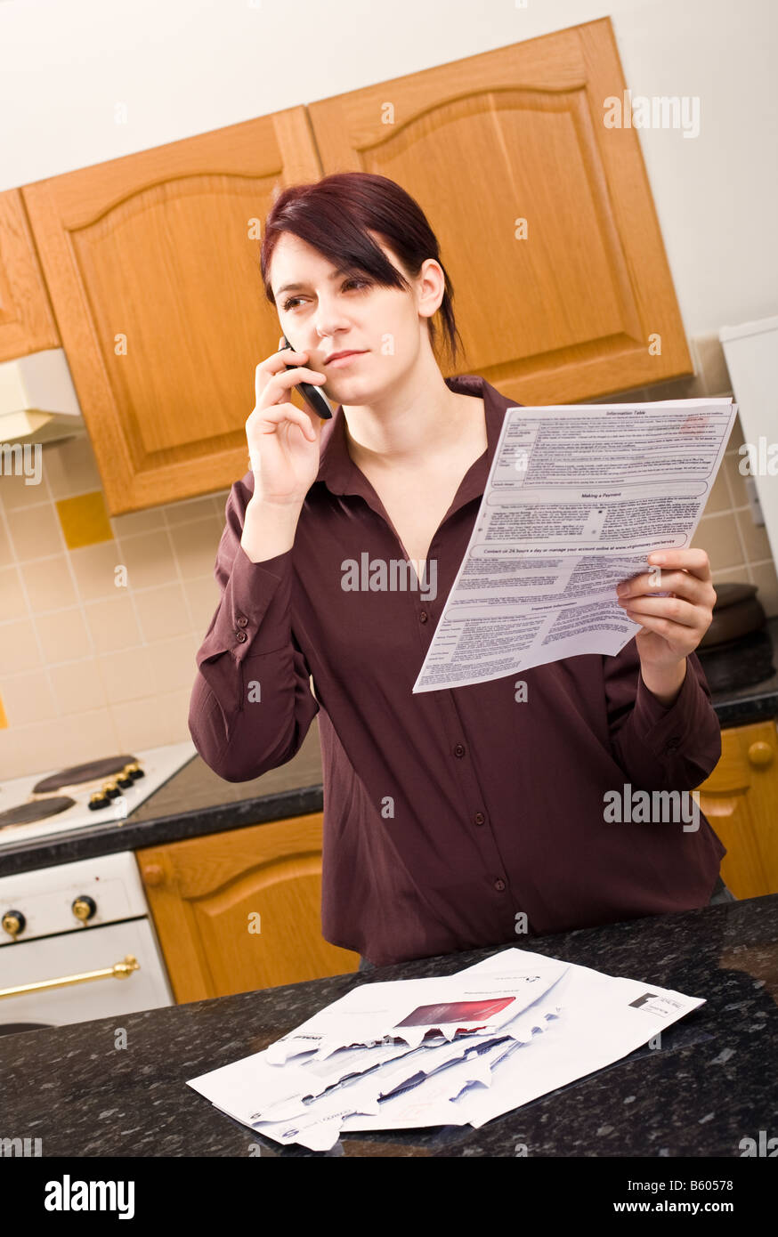 Young woman at home querying a large bill using her mobile phone listening and looking sceptical MR PR - Stock Image