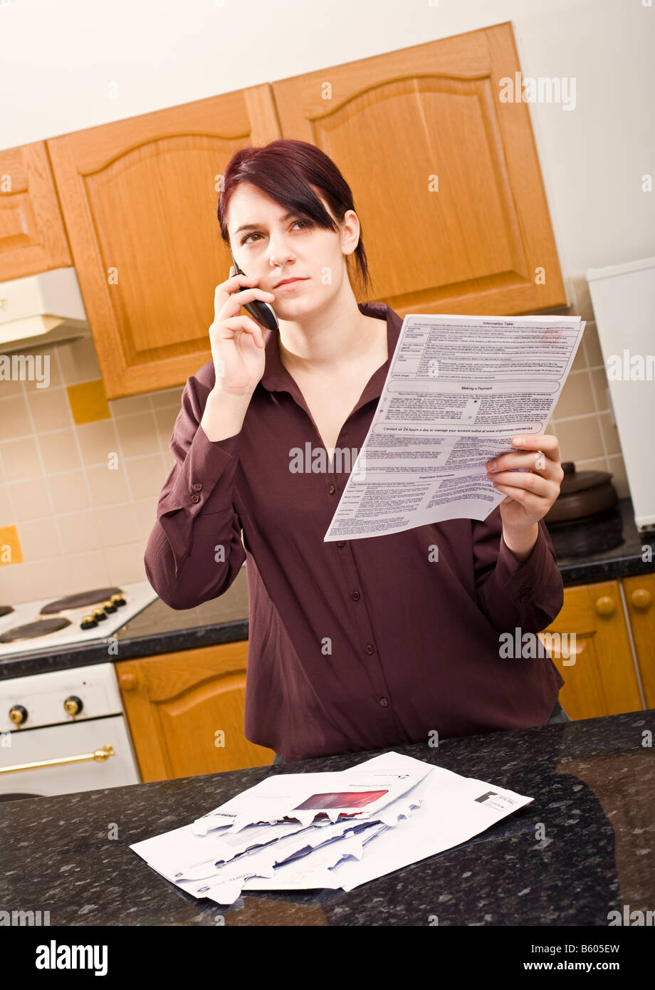 Young woman querying a large bill using her mobile phone listening and looking sceptical, serious expression - Stock Image