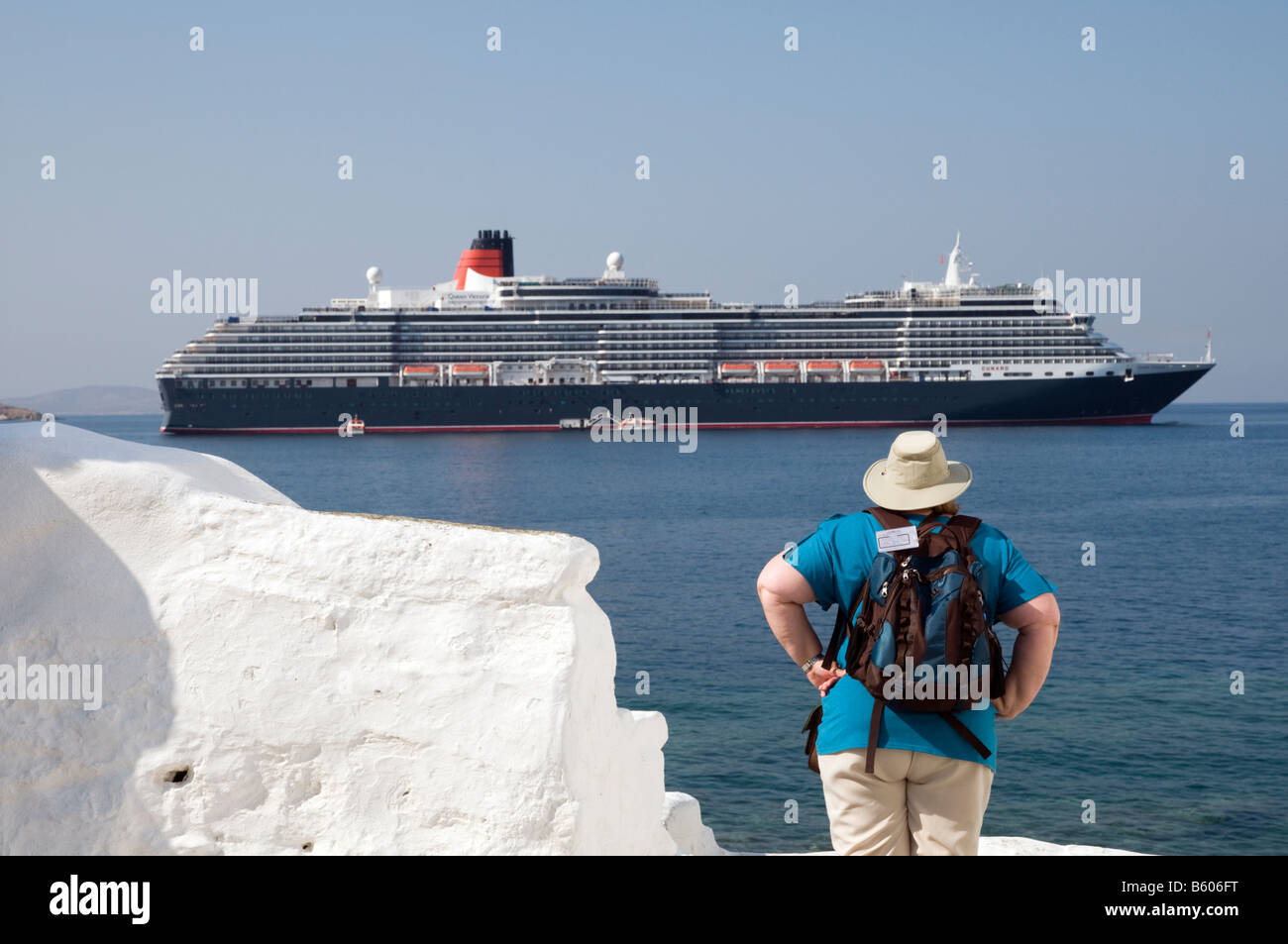 American tourists with Queen Victoria cruise ship in background on Mykonos, Greece - Stock Image