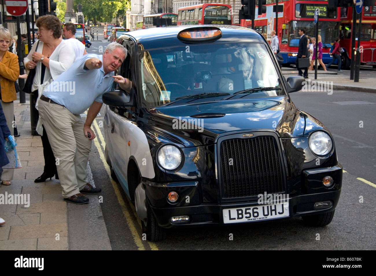 Hackney taxi cab driver giving directions to a pedestian in the city of London England - Stock Image