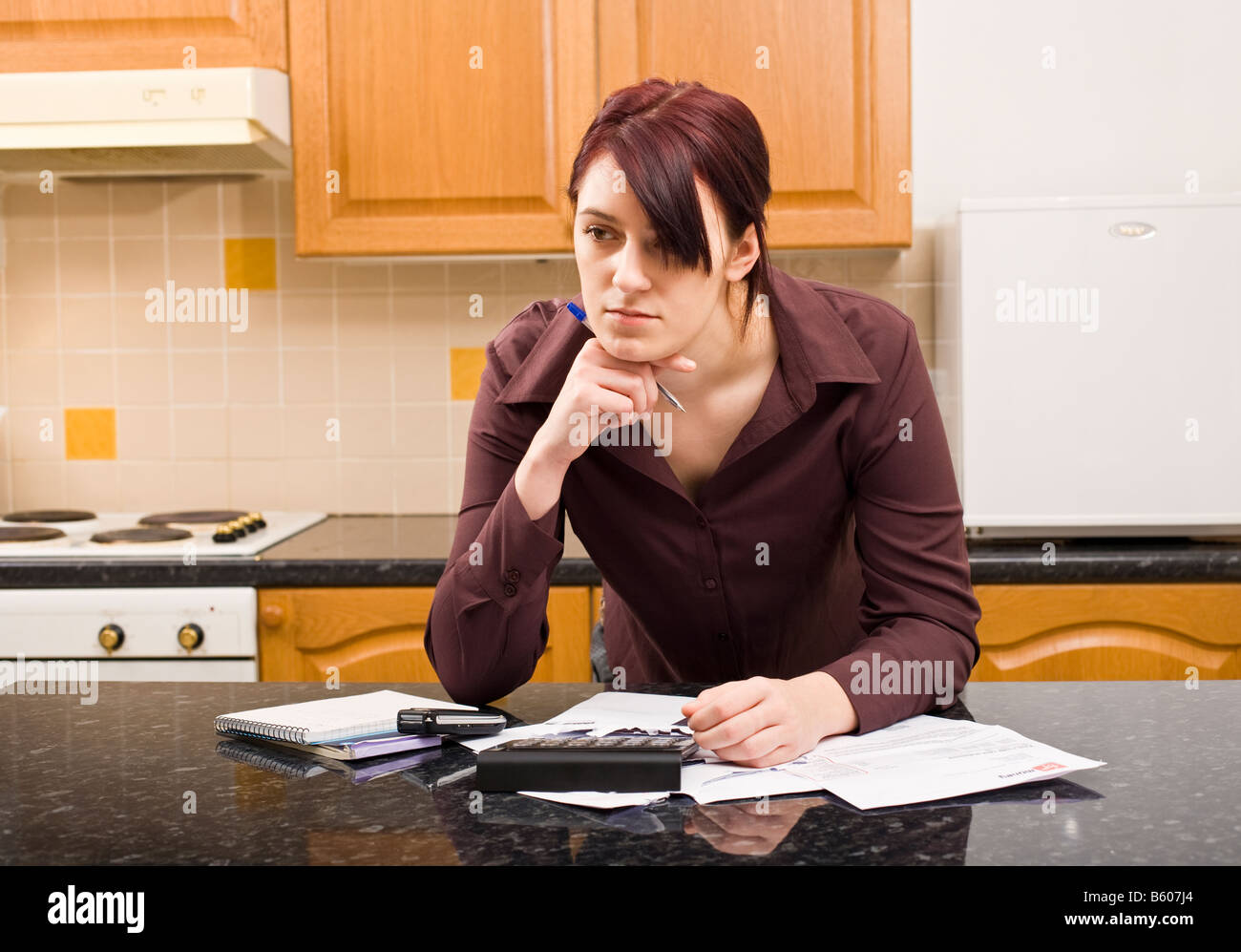 Young woman worried about household finances and budget with bills and calculator MR PR - Stock Image