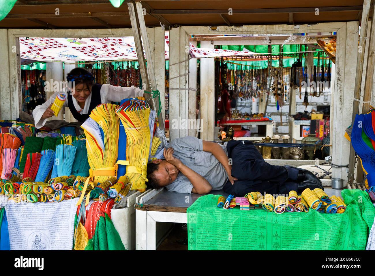 Stallkeeper sleeping on market stall in Barkhor Square Lhasa Tibet. JMH3665 - Stock Image