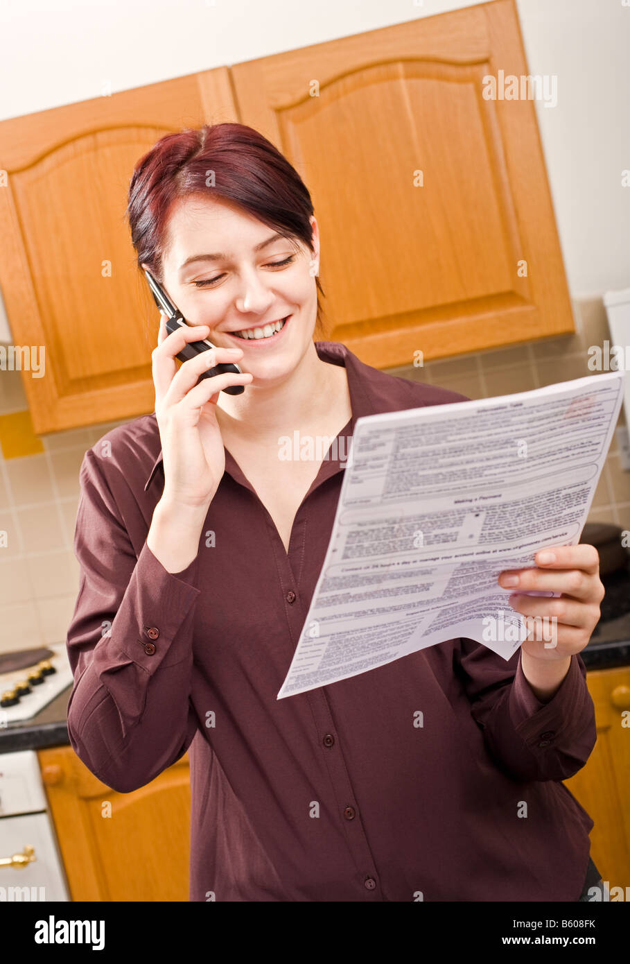 Young woman paying a bill using her mobile phone and smiling MR PR - Stock Image