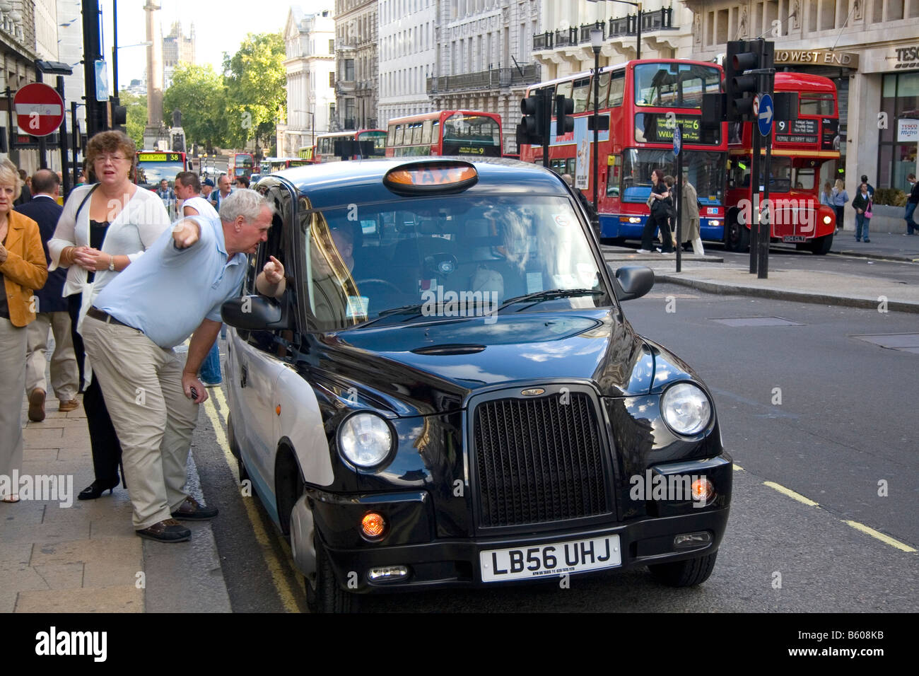 Hackney taxi cab driver giving directions to a pedestrian in the city of London England - Stock Image