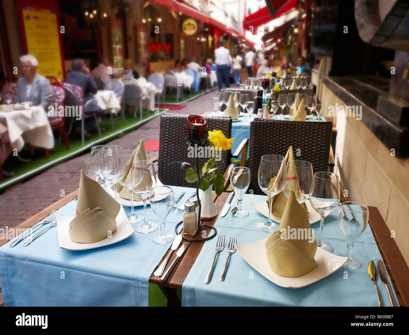 alleyway in old town with restaurants, well-laid table in front, Brussels, Brabant, Belgium - Stock Image