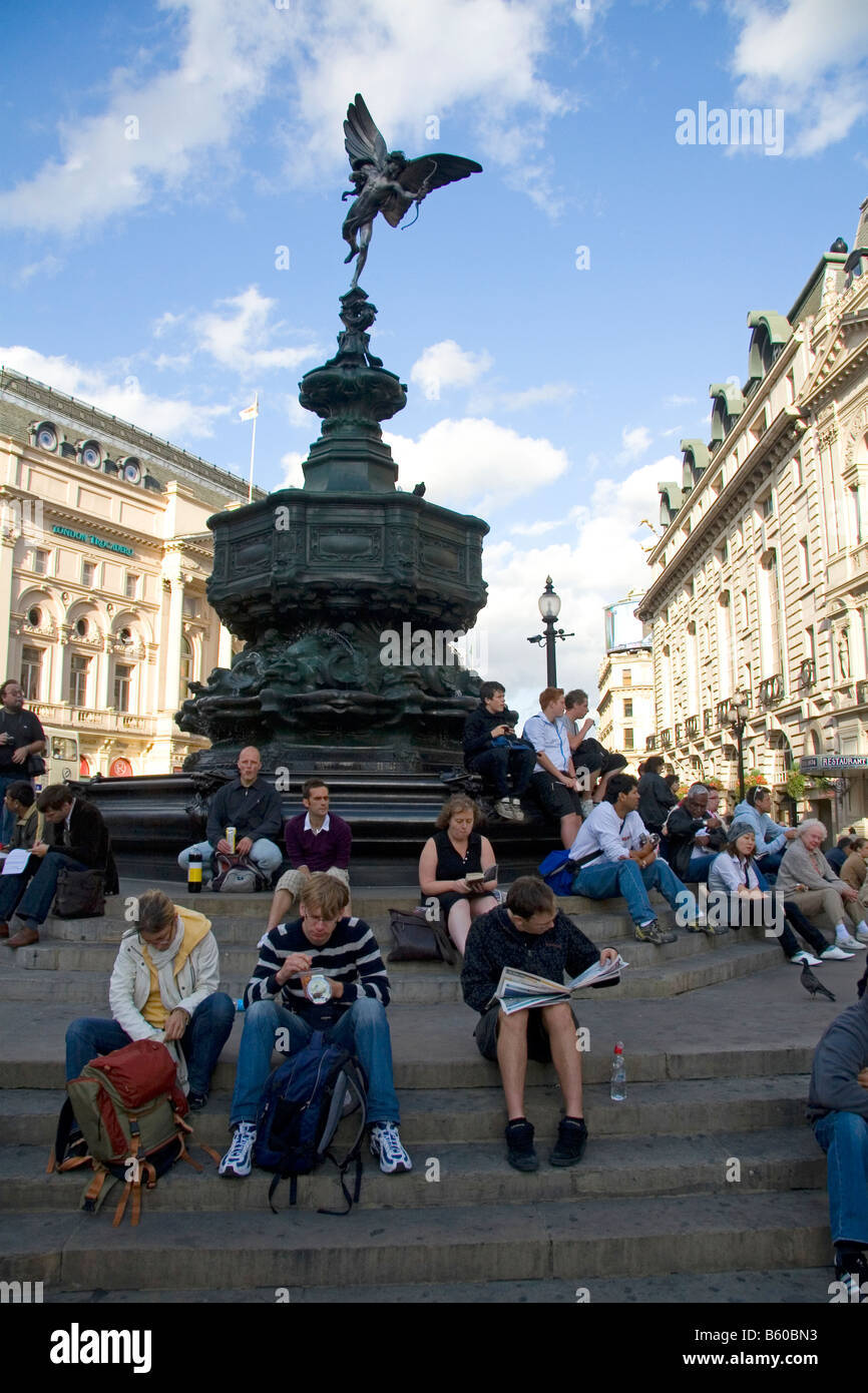 People sit on steps of the Shaftesbury Memorial Fountain in Piccadilly Circus London England - Stock Image
