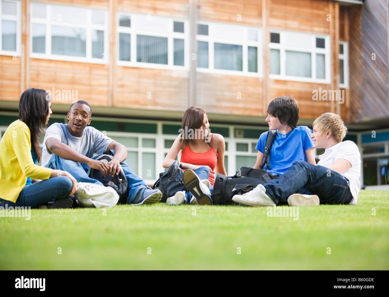 Five students sitting outdoors on lawn talking - Stock Image