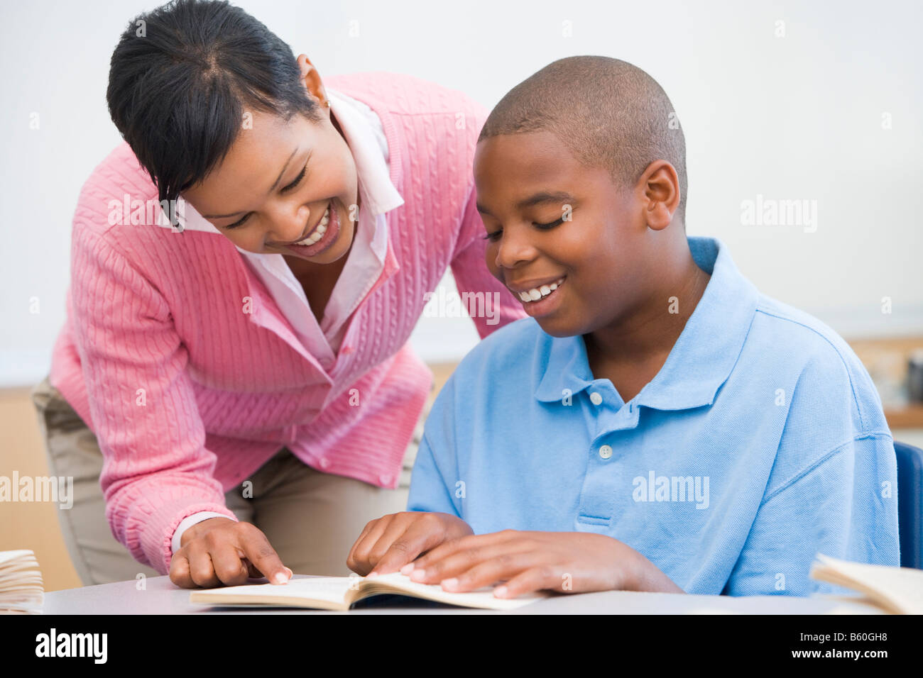 Student in class reading with teacher - Stock Image