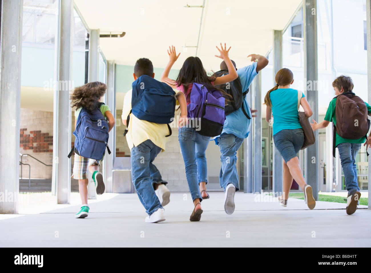 Six students running to front door of school excited - Stock Image