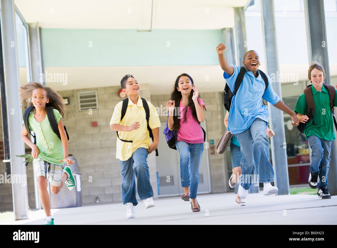 Six students running away from front door of school excited - Stock Image