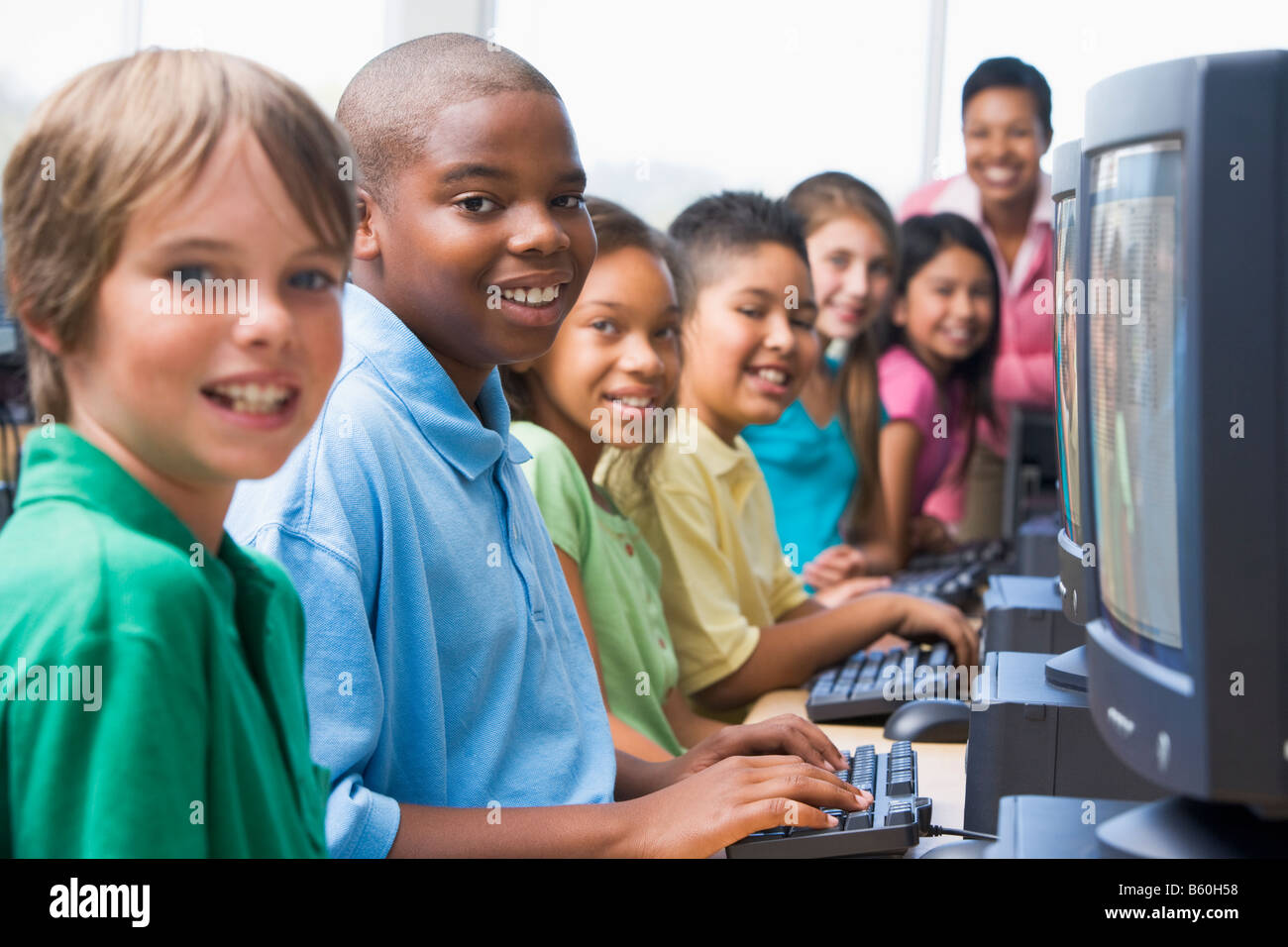 Six children at computer terminals with teacher in background (selective focus/high key) - Stock Image