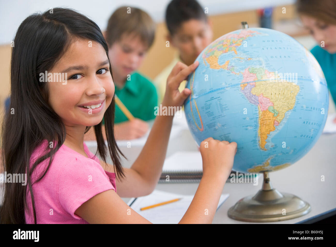 Student in class pointing at a globe (selective focus) - Stock Image