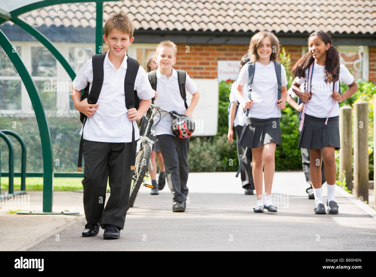Students leaving school one with a bicycle - Stock Image