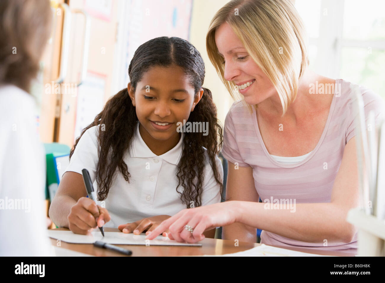 Student in class taking notes with teacher helping - Stock Image