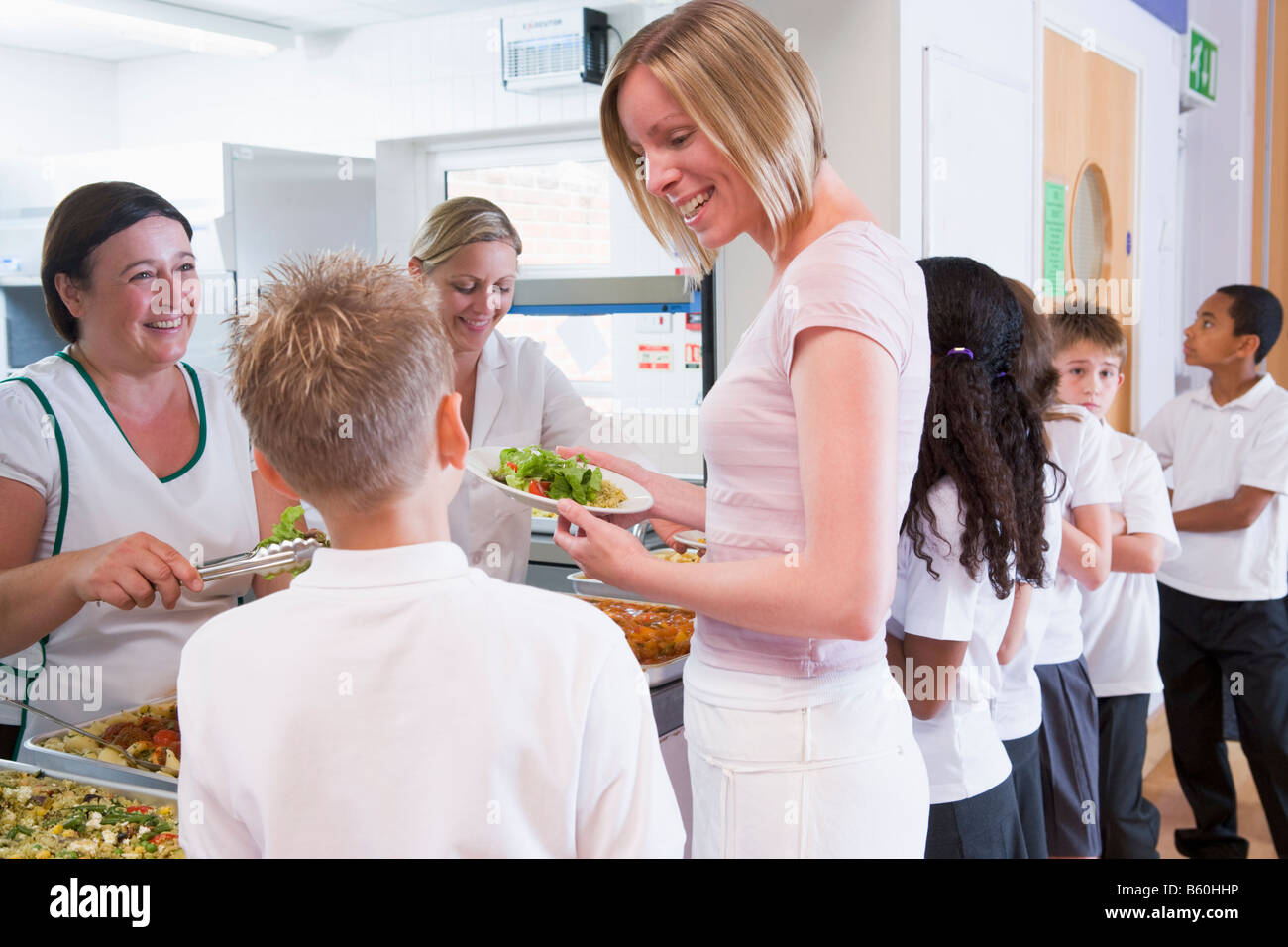 Students in cafeteria line with teacher at lunchtime - Stock Image