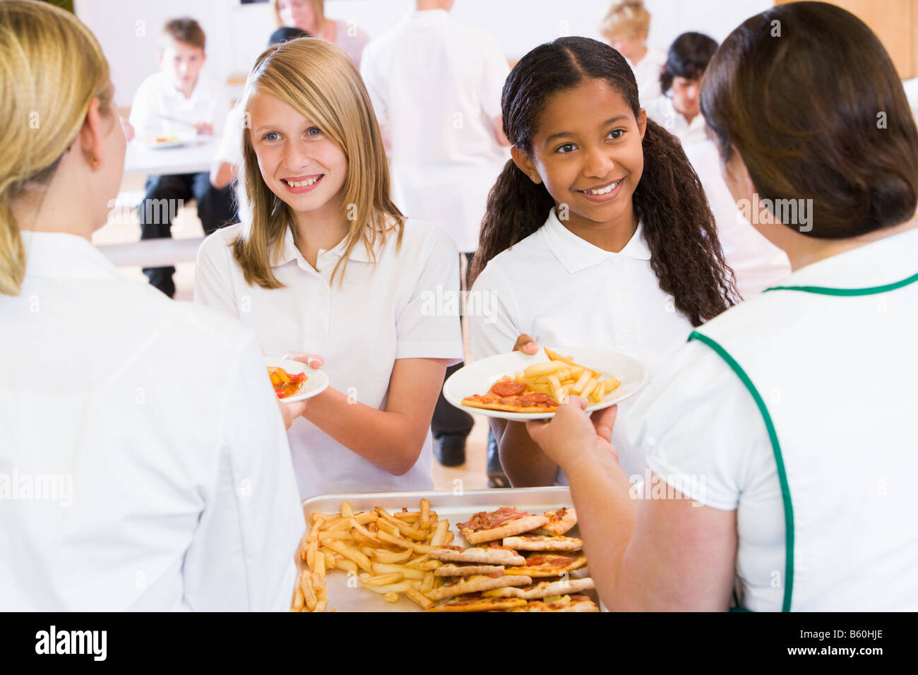 Students in cafeteria line being served by lunch ladies - Stock Image