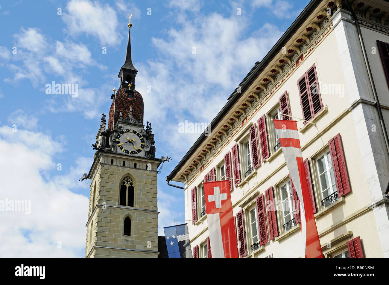 Steeple of the town church and a facade of a building with flags, Zofingen, Aargau, Switzerland, Europe - Stock Image