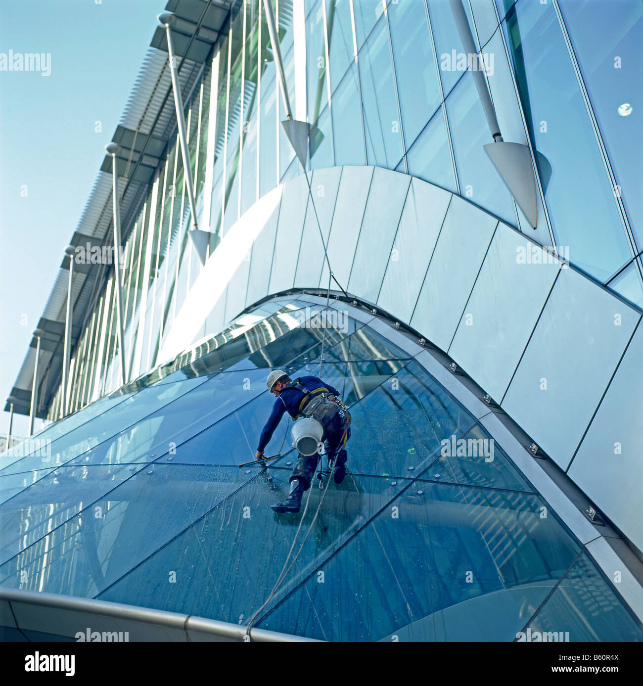 An immigrant worker cleaning windows on the foyer roof at Citypoint London Square Mile London England UK - Stock Image