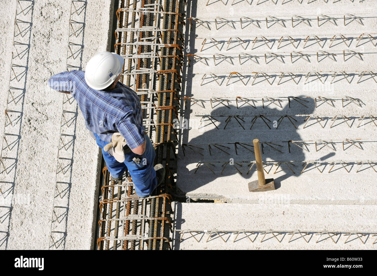 Laying a precast concrete ceiling, foreman inspecting the progress on the contruction site of an office building - Stock Image