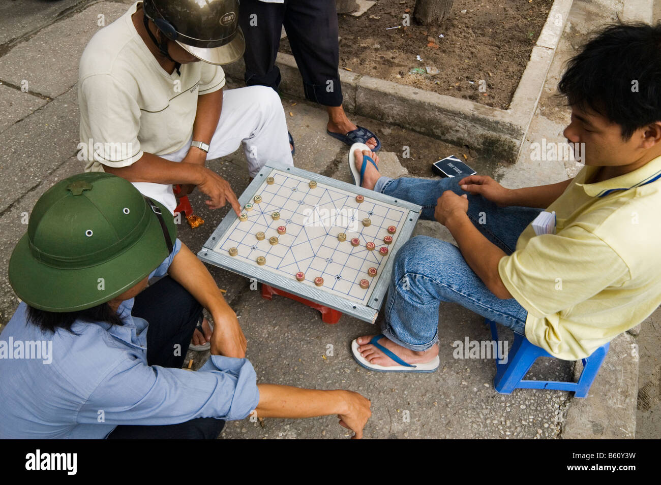 Men playing Vietnamese Chess - Co' tu'o'ng in the streets of Ho Chi Minh City, Vietnam - Stock Image