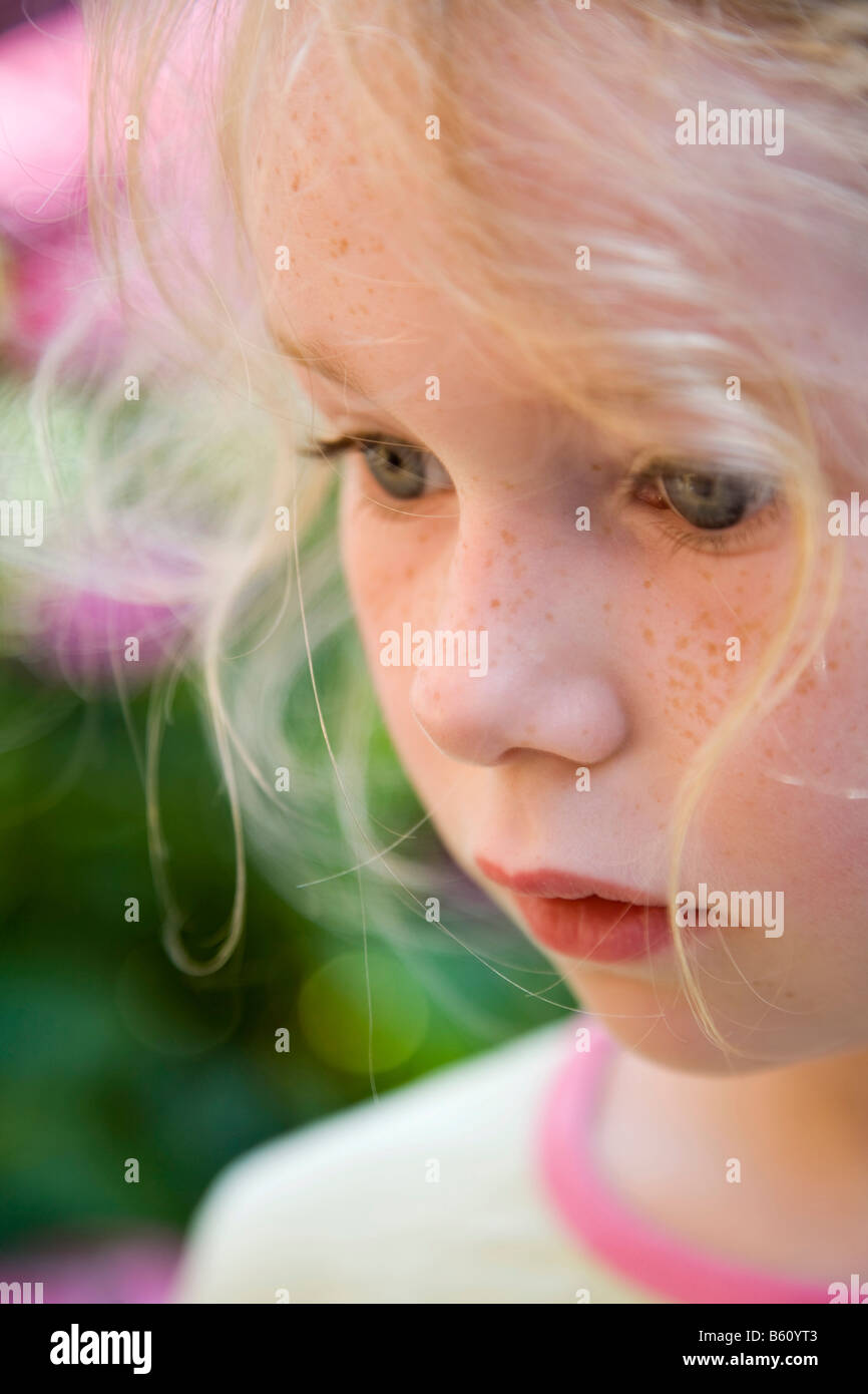 Portrait of a freckled girl, 5-10 years old, in a flower garden - Stock Image