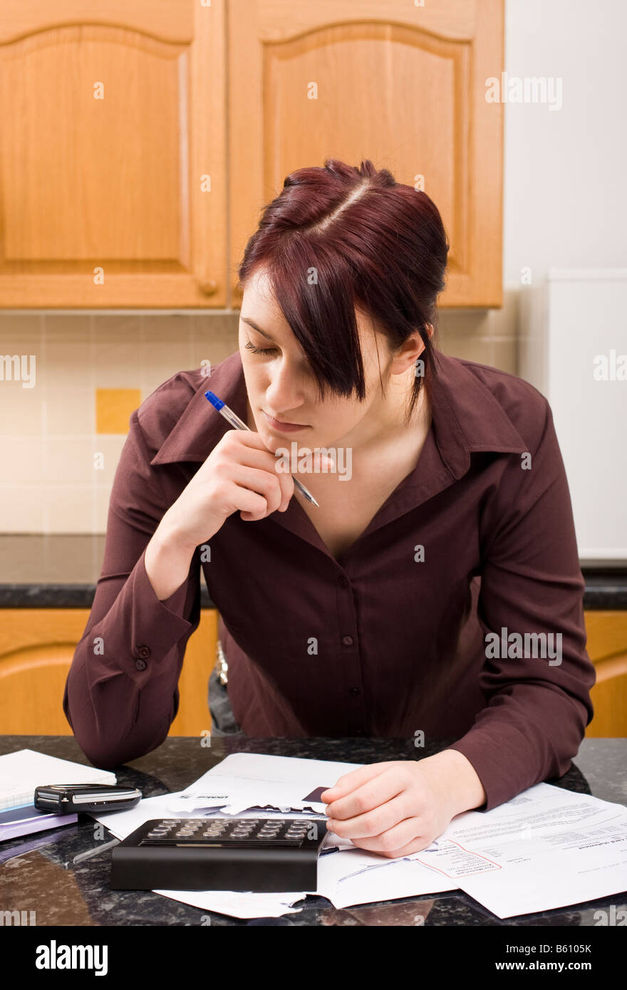 Young woman concentrating on household finances and budget with bills and calculator MR PR - Stock Image