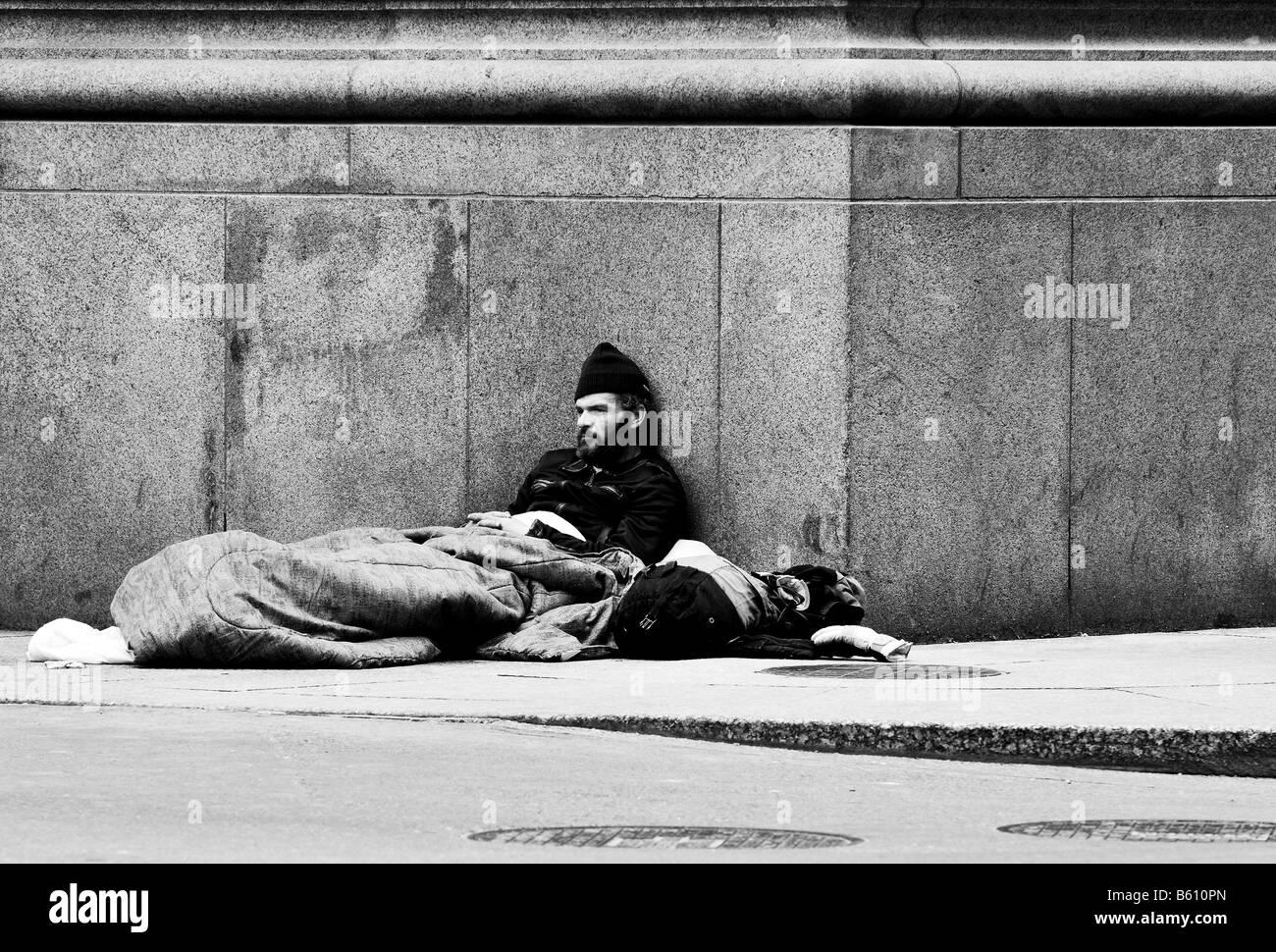 A black and white photo of a homeless man a bum a beggar sitting