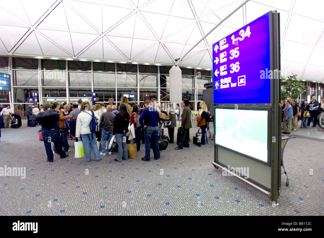 Wide angle view of passengers queing at a departure gate in Chek Lap Kok airport, Hong Kong. - Stock Image
