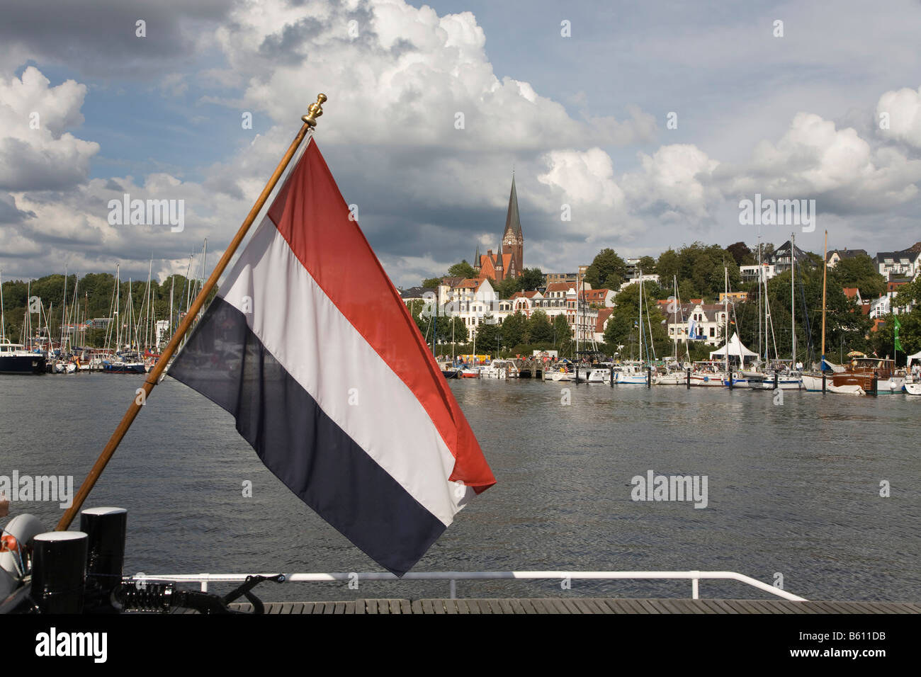 Flag of the Netherlands flying in front of the eastern shore of the Innenfoerde at the sail boat harbour and the - Stock Image