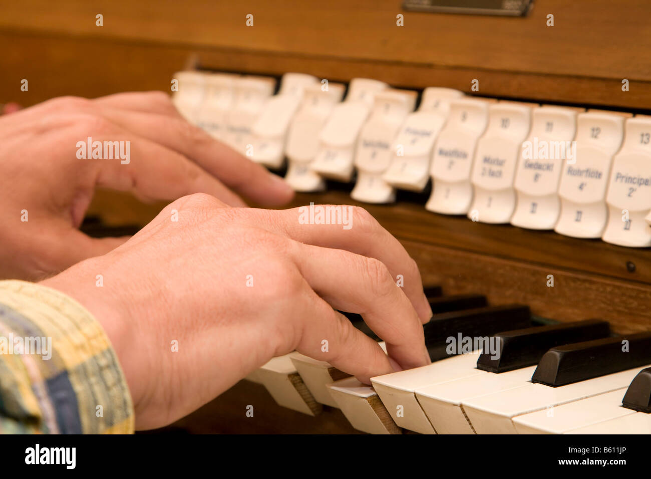 Hands operating the stops and keyboard, or manual, of the privately restored church organ at Orgelhof Goldelund, - Stock Image