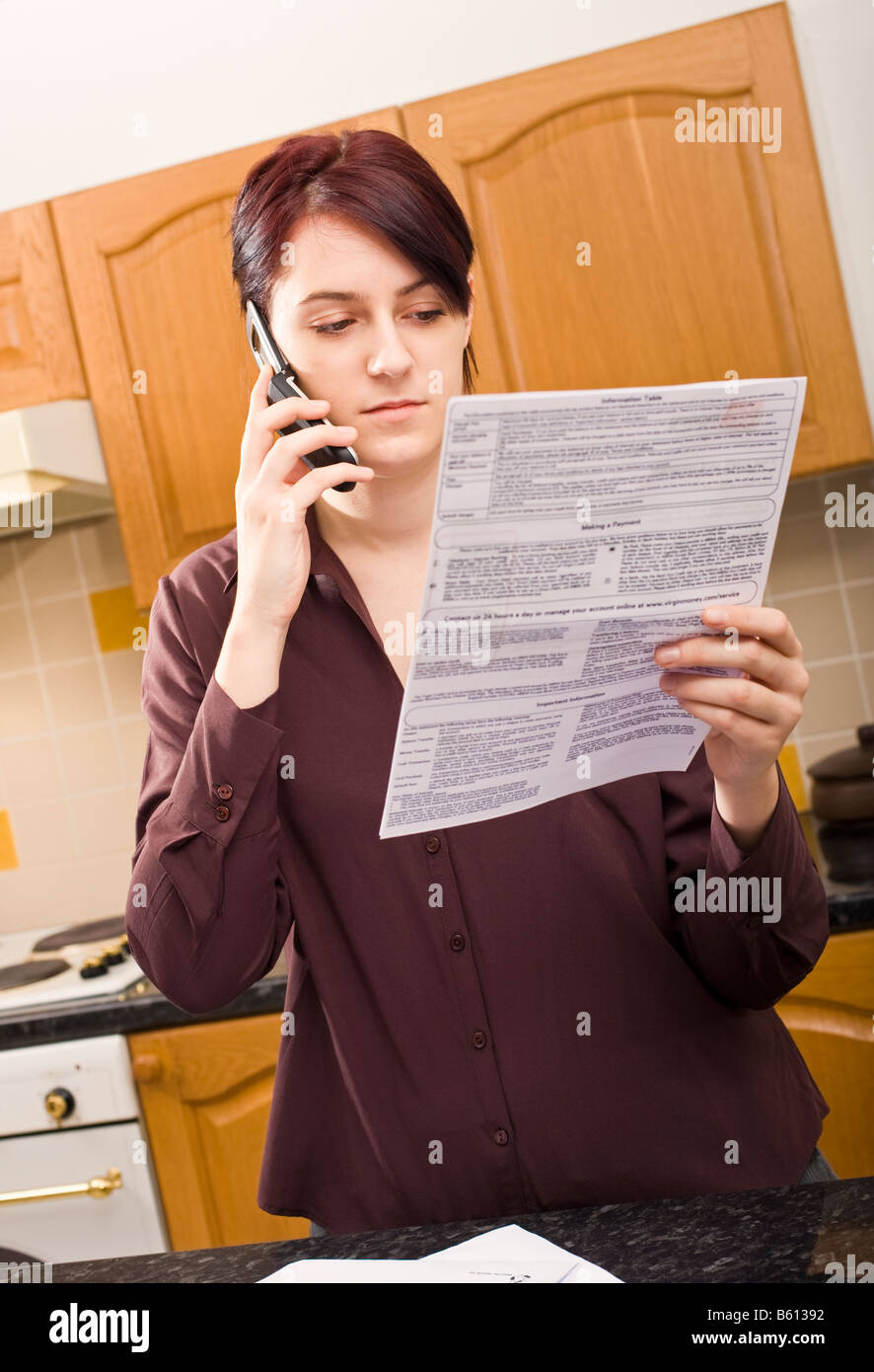 Young woman at home paying a bill using her mobile phone with serious expression,  listening and concentrating MR - Stock Image