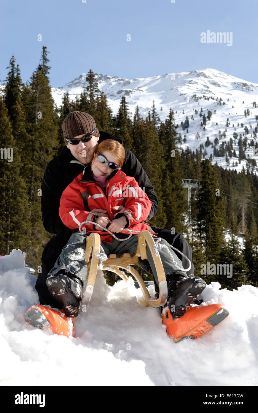 Father and daughter riding a sledge - Stock Image
