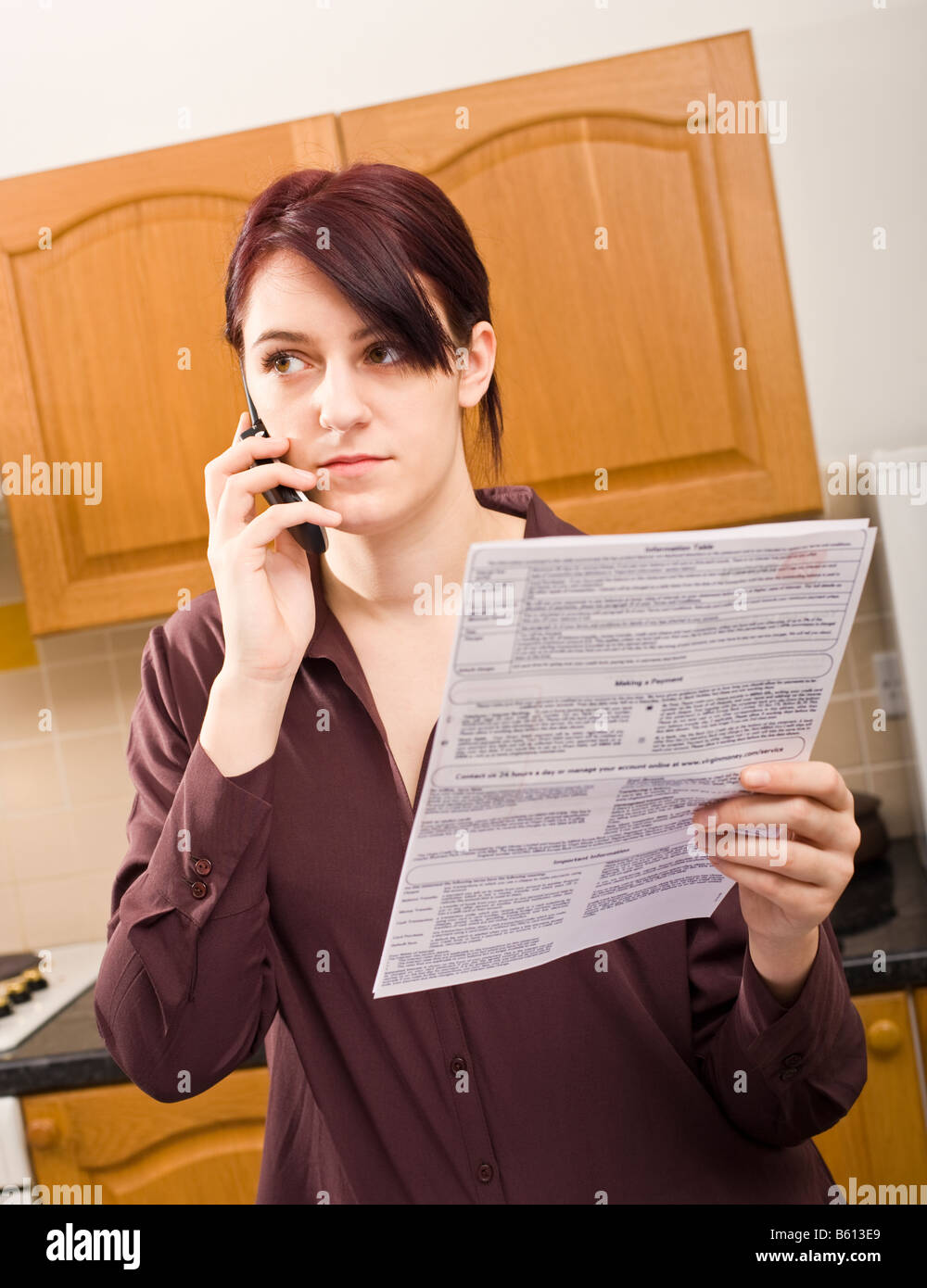 Young adult woman at home querying a large bill using her mobile phone listening and concentrating looking away - Stock Image