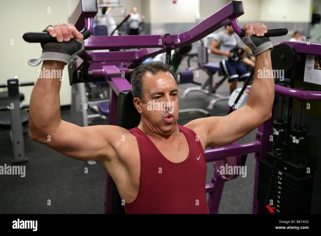A 61-Year-old man works out in a gym. The man, who has a family history of Heart disease works out to improve his - Stock Image