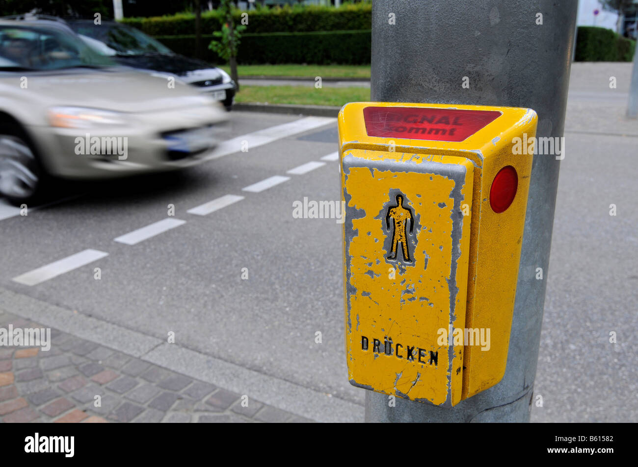 Crossing light request button for pedestrians, label 'signal coming' is lit, blurred car at back, Stuttgart, - Stock Image